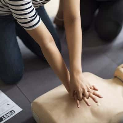 Woman performing first aid chest compression